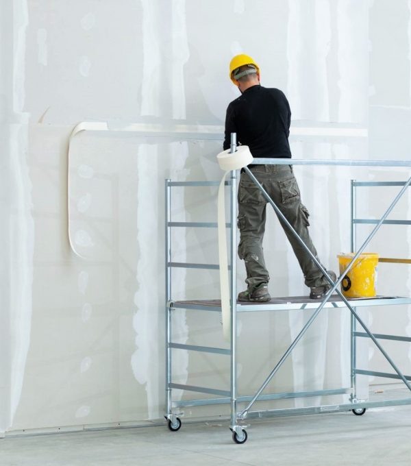 Interior construction, worker plastering gypsum board wall.